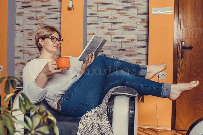 中间年迈的妇女看书和饮用的咖啡在家 库存图片