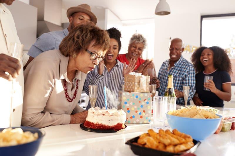 中间年迈的非裔美国人的妇女切口蛋糕在三一代家庭生日庆祝时,关闭  免版税库存照片
