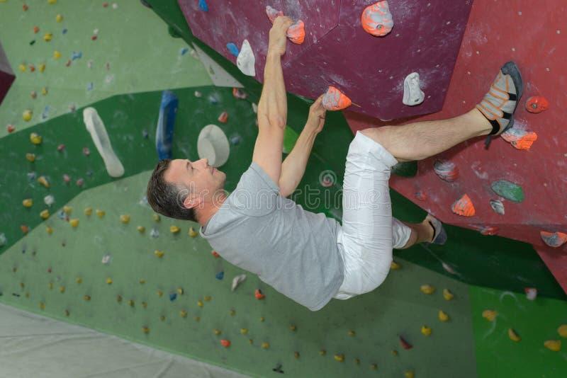 中间年龄在人为上升的墙壁上的人登山人 库存图片