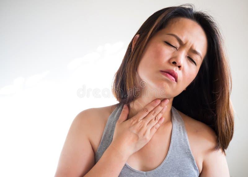 中间成人亚裔妇女喉咙痛和接触使用的手  库存图片