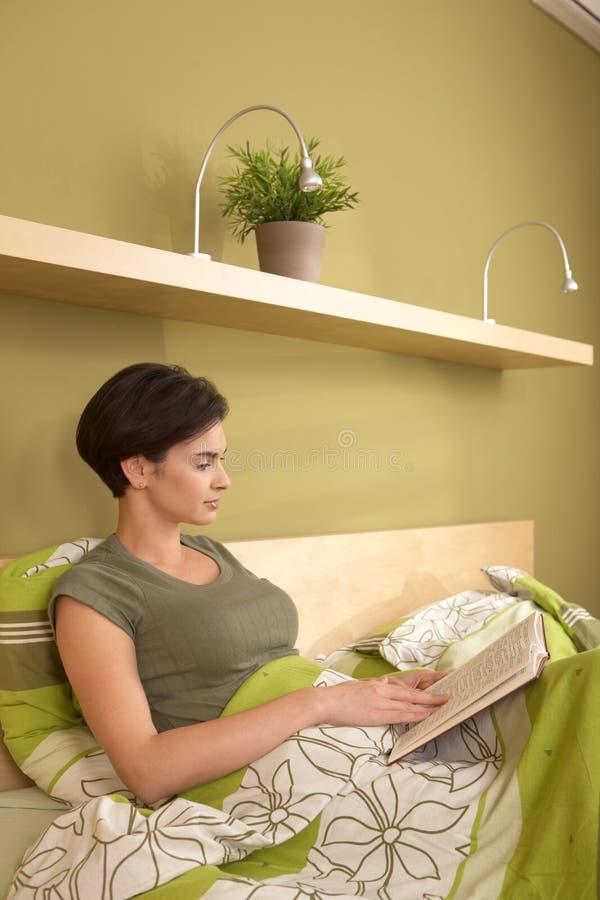中间成人俏丽的妇女读取在卧室 免版税库存照片