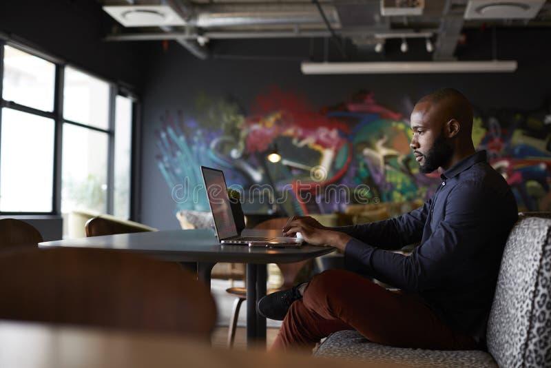 中间成人黑男性创造性的开会在桌上在办公室饭厅使用膝上型计算机,侧视图 图库摄影