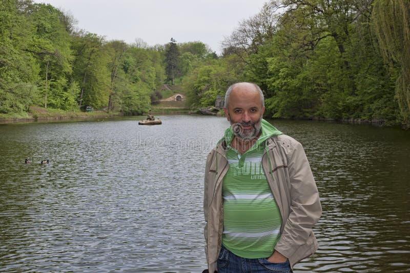 中年人在湖的背景中 库存图片