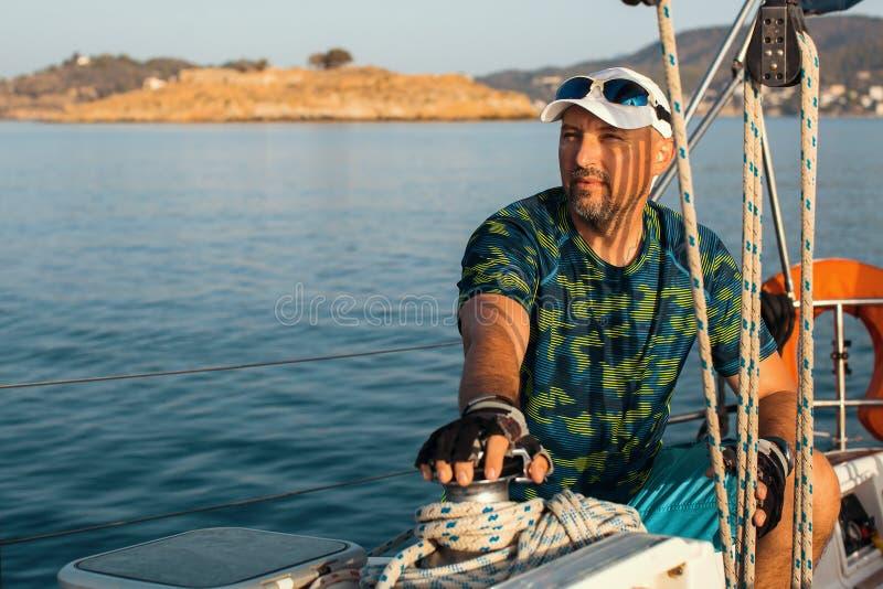 中年人坐他的游艇 库存图片