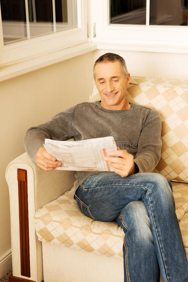 中年人读书报纸在家 免版税库存图片