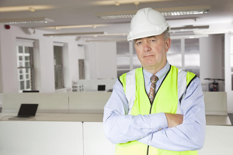 中年人画象反射器背心和安全帽的在办公室 免版税库存照片