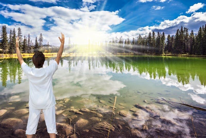 中年妇女,打扮为瑜伽,太阳致敬 免版税库存照片