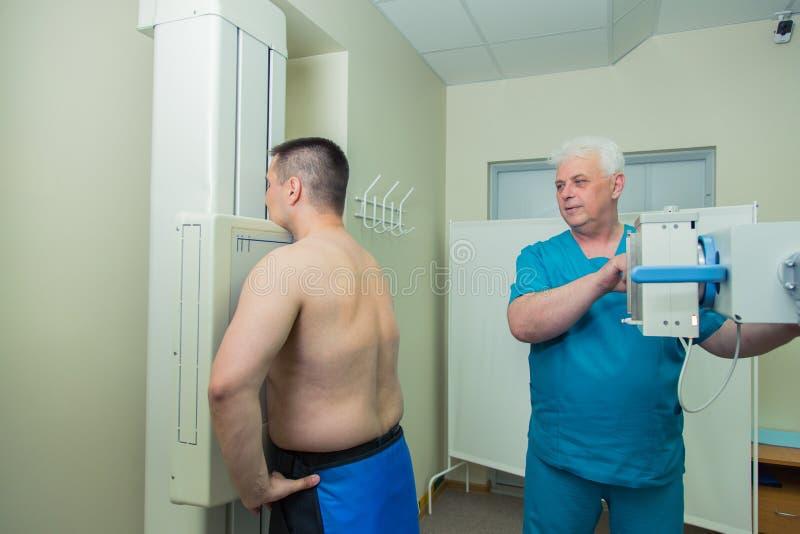 中间成人设定机器的人耐心成熟男性医生采取X-射线 库存照片