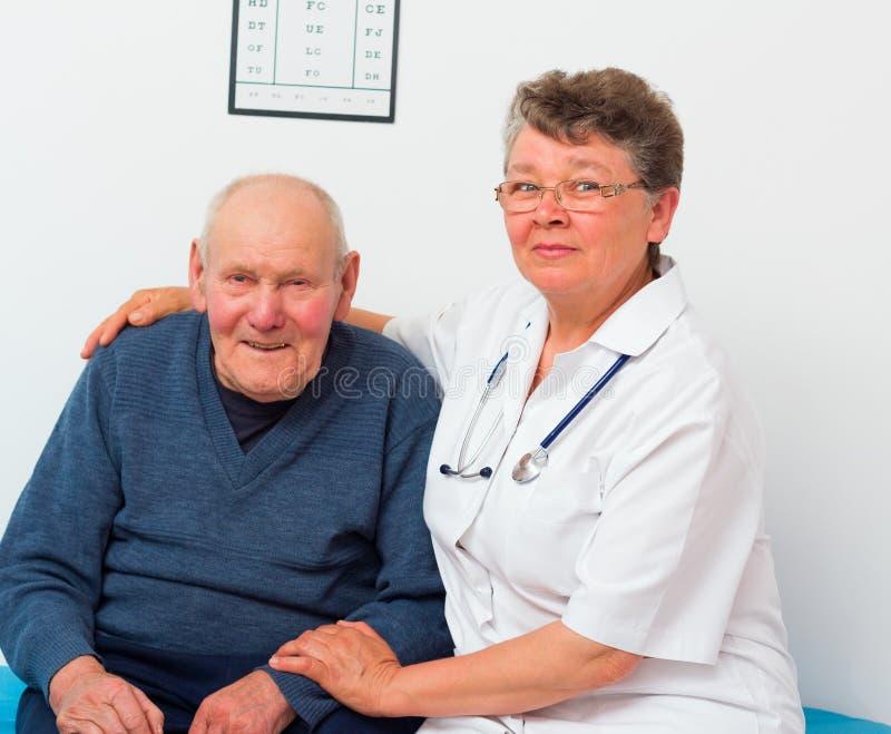 中年医生With Elderly Patient 库存图片
