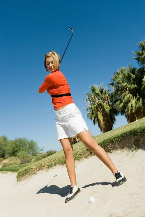 击中从砂槽的女性高尔夫球运动员球 库存图片