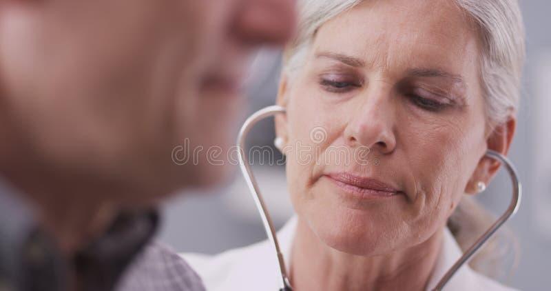 中间年迈的医生谈话与男性患者 免版税库存图片