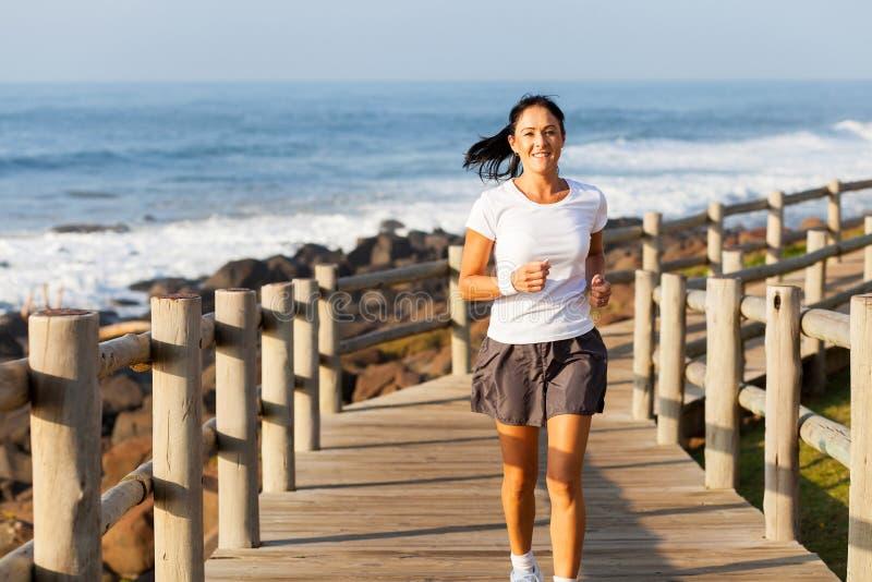 中间年龄妇女跑步 免版税库存照片