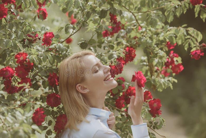 丰富开花 有红色花的性感女孩在夏天庭院里 有花绽放的可爱的女孩 俏丽的女孩在 免版税库存图片
