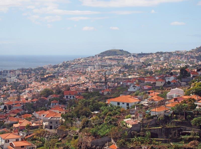 丰沙尔的顶上的全景在有城市的屋顶和地标的马德拉可看见在海前面 库存照片