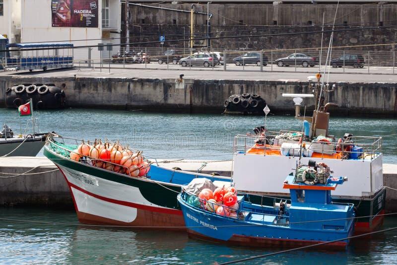 丰沙尔,马德拉,葡萄牙- 2018年7月22日:渔夫和在丰沙尔港的明亮的浮游物小船有网的  免版税库存图片