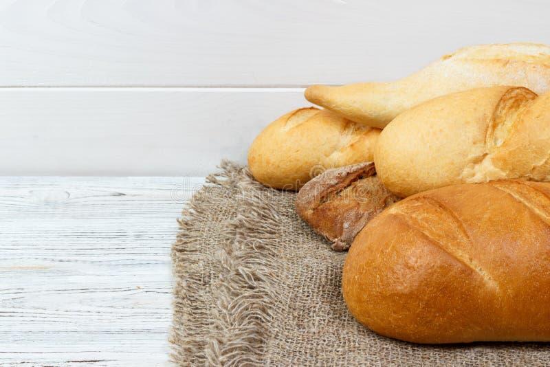 丰足面包背景 面包店和杂货概念 新鲜,健康黑麦和白色大面包,在麻袋布的被洒的面粉和土气 免版税库存图片