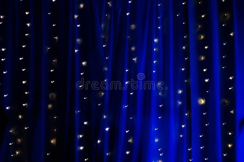 串彩色小灯长的曝光在蓝色有启发性帷幕的 免版税库存照片
