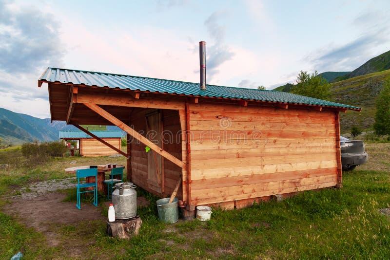 临时生活的一个简单的木房子在阿尔泰山的夏天与在屋顶的一个烟囱在一个美丽如画的地方 库存照片