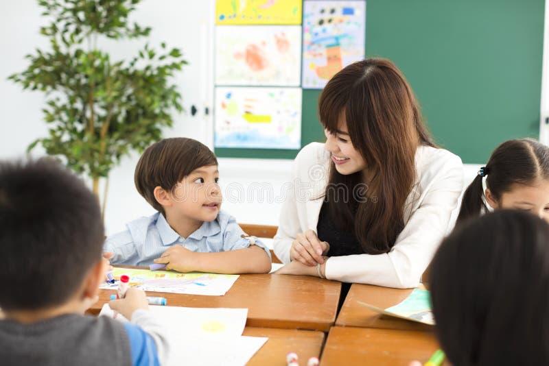 临近在教室和老师的孩子  库存图片