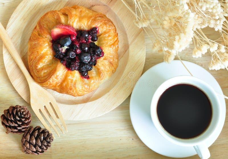丹麦莓果用在木板材的浓咖啡 免版税库存图片
