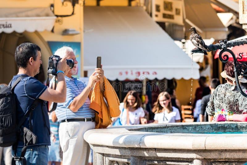 为一个喷泉照相的两个游人人在希波克拉底广场在罗得岛奥尔德敦,希腊 库存图片