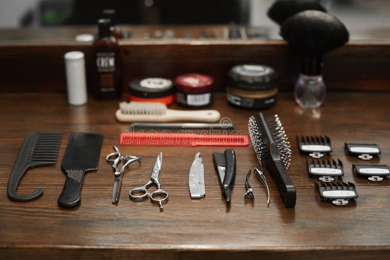 为一位美发师的工具在一张黑暗的木桌上在理发店-剪刀、喷管、梳子和剃刀 免版税库存图片