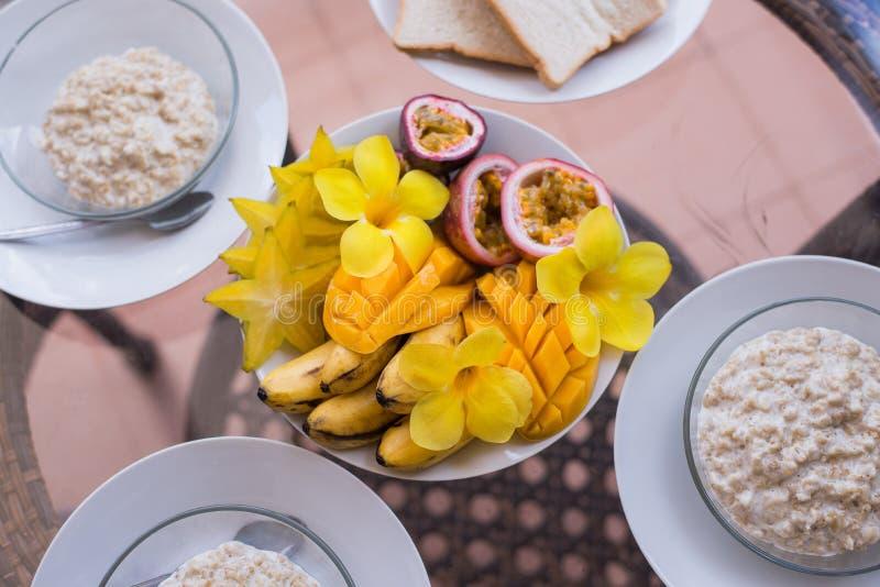 为三人供应的可口家庭早餐 Oatmeals porrige和水果钵用芒果,香蕉, passionfruit和 免版税库存照片