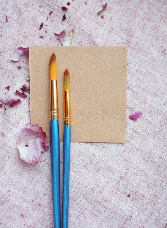 为与刷子和紫色玫瑰花瓣的艺术品注意假装  库存图片