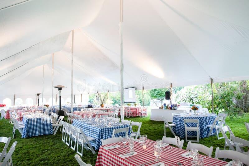 为与红色和蓝色方格的桌衣裳的一串室外烤肉设定的婚礼或特别活动桌在事件帐篷下 免版税库存图片