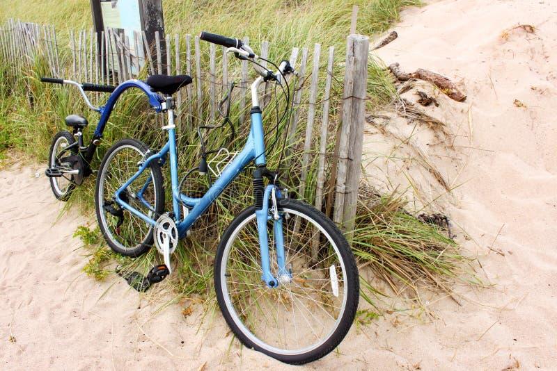 为两制造的自行车倾斜在篱芭由海滩和沙丘 图库摄影