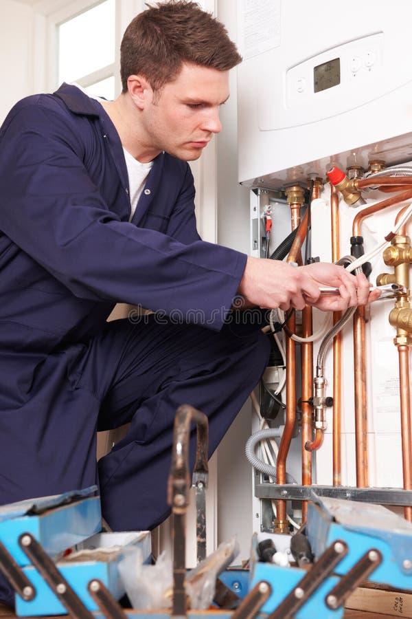 为中央系统暖气锅炉服务的工程师 免版税库存照片