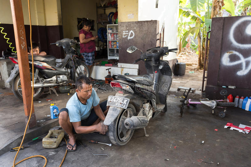 为人修理放气的损坏的轮胎服务 库存图片