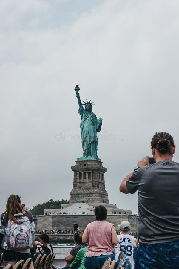 为从一条游览小船的游人自由女神像照相在哈得逊河,纽约,美国 免版税图库摄影