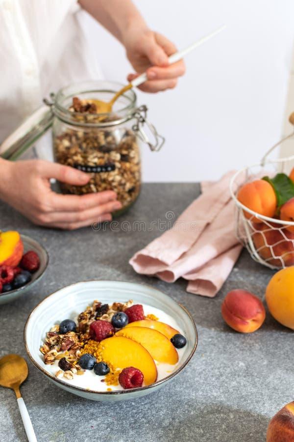 为从瓶子的女性手格兰诺拉麦片服务,用希腊酸奶新鲜的桃子,蓝莓,在桌上的莓-健康早餐 免版税库存图片