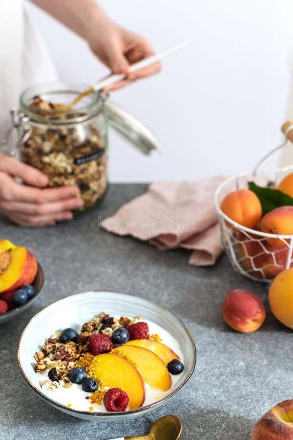为从瓶子的女性手格兰诺拉麦片服务,用希腊酸奶新鲜的桃子,蓝莓,在桌上的莓-健康早餐 免版税图库摄影