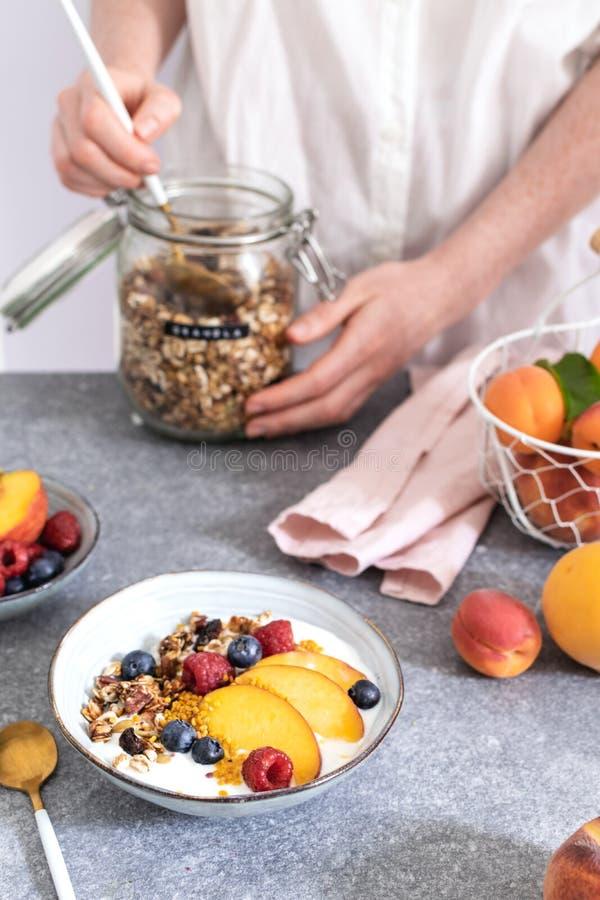 为从瓶子的女性手格兰诺拉麦片服务,用希腊酸奶新鲜的桃子,蓝莓,在桌上的莓-健康早餐 库存照片