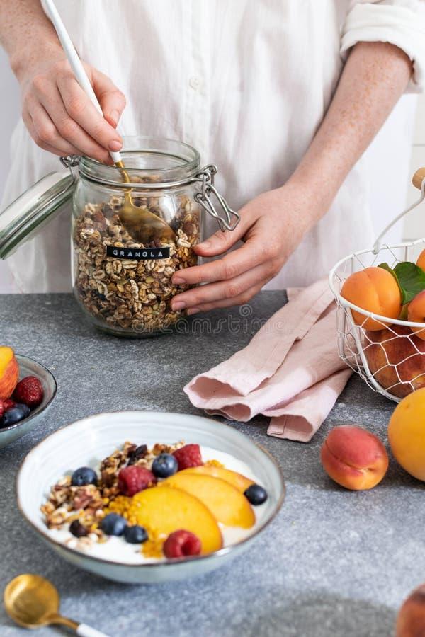 为从瓶子的女性手格兰诺拉麦片服务,用希腊酸奶新鲜的桃子,蓝莓,在桌上的莓-健康早餐 图库摄影