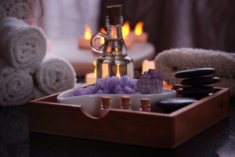 为从石头按摩的,油,紫罗兰谎言海盐的温泉做法设置在一个木箱的 在a的潮湿毛巾谎言 免版税库存图片
