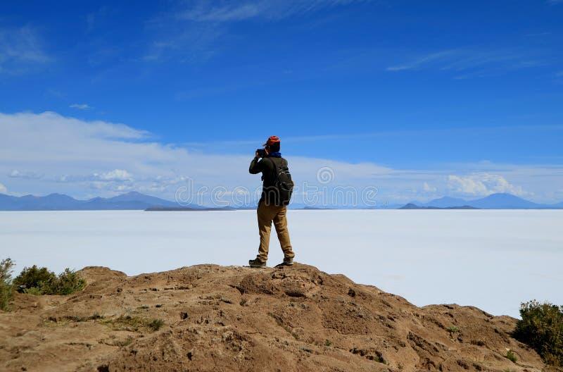为从Isla印加瓦西峰,在盐舱内甲板中间的露出的一个男性游人巨大Uyuni盐舱内甲板照相 库存照片