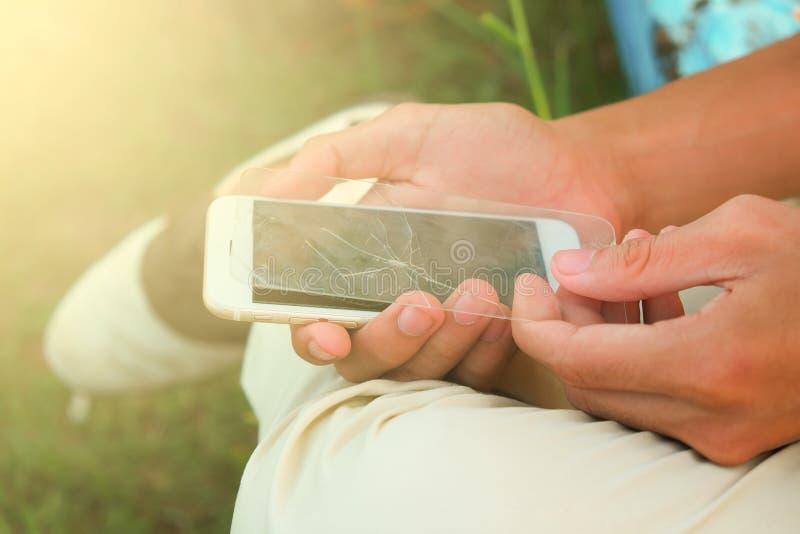 为使用发生手机/保护胶卷是残破的保护胶卷拘捕的人 免版税库存图片