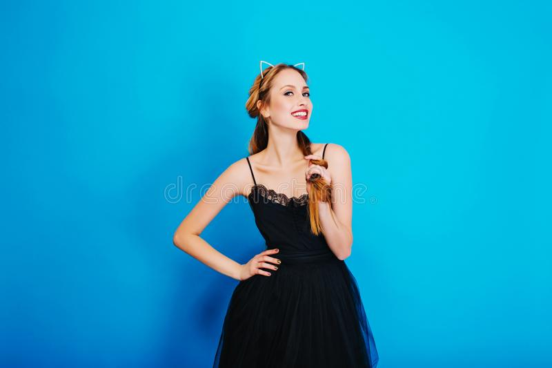 为党打扮的年轻俏丽的女孩,化妆舞会,狂欢节,微笑和摆在蓝色背景 佩带的时髦的黑色 免版税库存照片