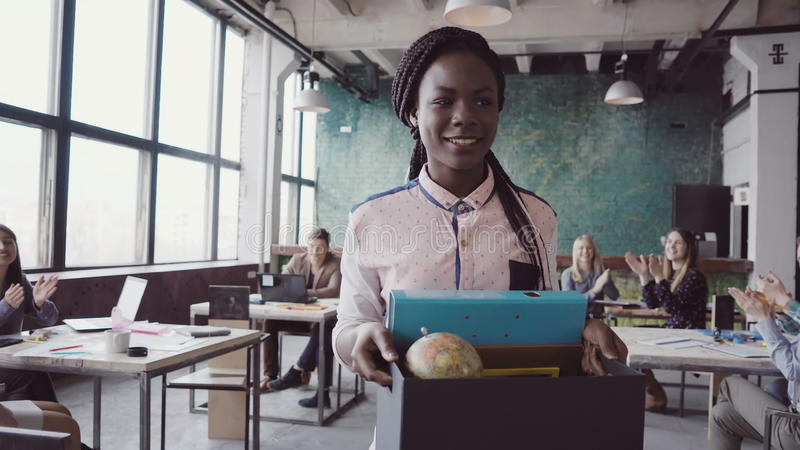为公司工作最近雇用的年轻非洲妇女进入新的办公室 女性拿着有个人财产的箱子 免版税图库摄影