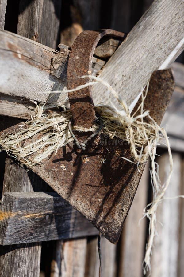农夫的工具_老,生锈的锄,放置在谷仓的墙壁;为农夫的古老工具