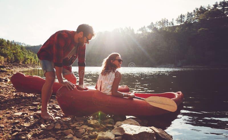 去为划皮船的夫妇在湖 免版税库存图片