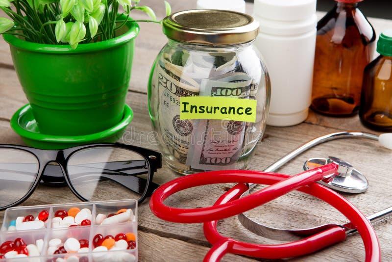 为医疗保险省钱-钱杯、听诊器、药丸和瓶 免版税库存照片