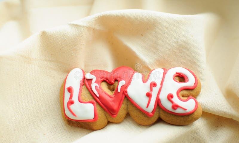 为华伦泰` s天在曲奇饼上写字或在粗糙的白棉布织品背景的一婚礼之日  库存图片