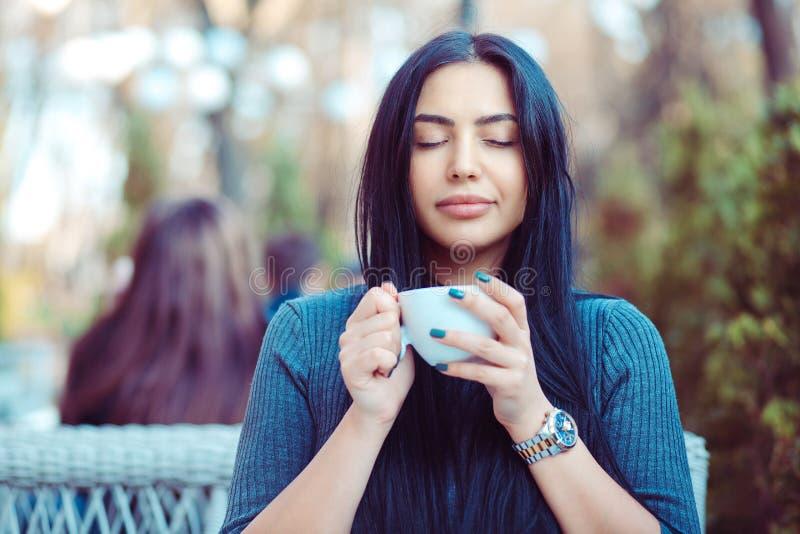为咖啡爱 喝逗人喜爱的女孩的画象享用她的在阳台的茶在外部大阳台有绿色灌木背景, w 库存图片