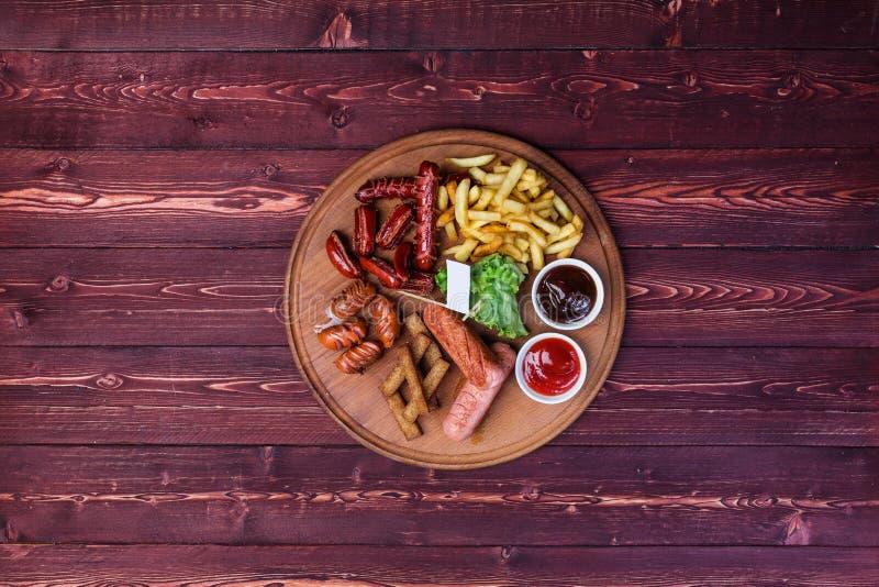 为啤酒设置的香肠 香肠、薯条、薄脆饼干、番茄酱和调味汁在切板和木背景 免版税库存照片