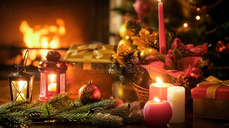 为圣诞节装饰的木桌的特写镜头图象反对灼烧的壁炉在客厅 免版税图库摄影