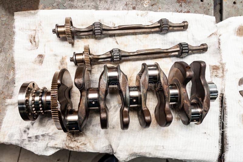 为在一个工作凳的替换去除的汽车曲轴的特写镜头在车维修车间 汽车工业 免版税库存图片